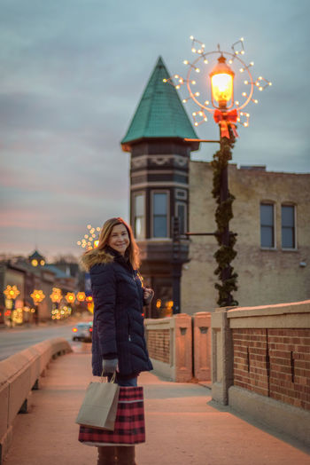 Carrying Christmas Shopping Architecture Bags Building Exterior City Decorations Dusk Focus On Foreground Full Length Illuminated Lifestyles Night One Person Outdoors People Real People Sky Street Light Street Lights Walking Warm Clothing Young Adult Young Women