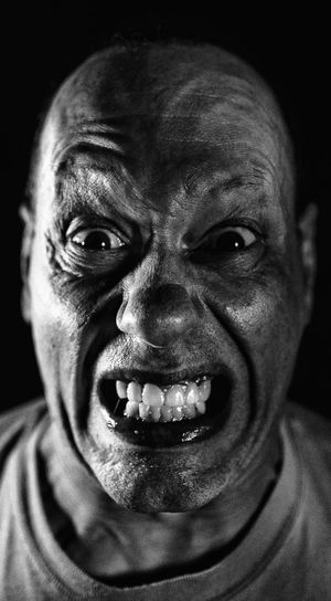 Close-up portrait of angry man against black background