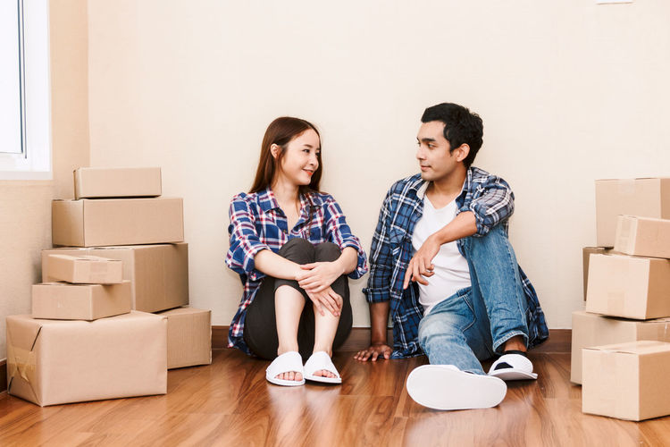 Happy couple with cardboard box at new home Adult Beginnings Box Boyfriend Cardboard Cardboard Box Change Couple - Relationship Flooring Full Length Girlfriend Happiness Heterosexual Couple Indoors  Living Room Moving House Packing Relocation Togetherness Two People Unpacking Women Young Adult Young Couple Young Women