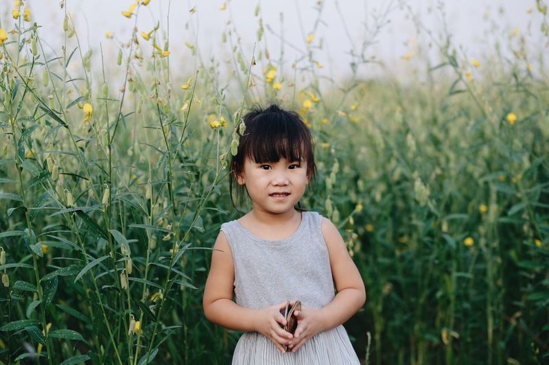 Portrait of girl standing by flowering plants