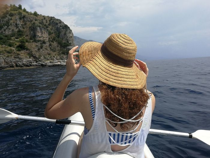 Girl in a canoe along the coast while arranging her hat to protect herself from the sun Maratea, Girl, Tourist, Canoe, Cave, Sea, Mediterranean, Sunny, Coast, Coastal, Cliff, Gulf, Bay, Water, Shore, Waves, Blue, Summer, Holiday, Tourism, Backdrop, Hand, Arm, Female, Curly Hair , Back, Back, Costume, Model, Straw, Beauty In Nature Clothing Day Hairstyle Hat Holiday Leisure Activity Lifestyles Mode Of Transportation Nature Nautical Vessel One Person Outdoors Real People Sea Transportation Trip Vacations Water Young Adult First Eyeem Photo