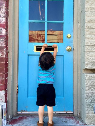 Rear view of boy holding door