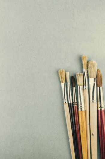 paintbrushes Minimalist Art And Craft Art And Craft Equipment Brush Choice Close-up Colored Background Copy Space Craft Creativity Directly Above Group Of Objects High Angle View Indoors  No People Paintbrush Still Life Studio Shot Variation White Background Wood - Material