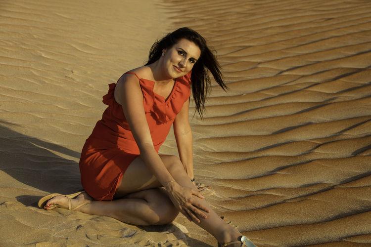 Portrait of woman sitting on sand dune at desert