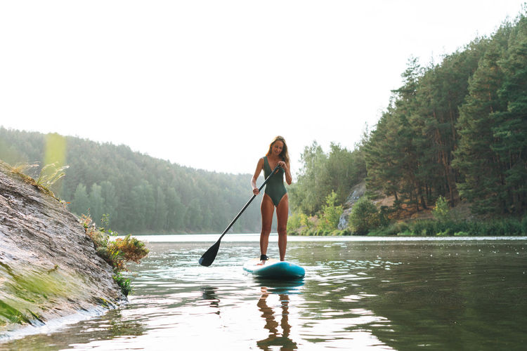 Woman in lake against sky