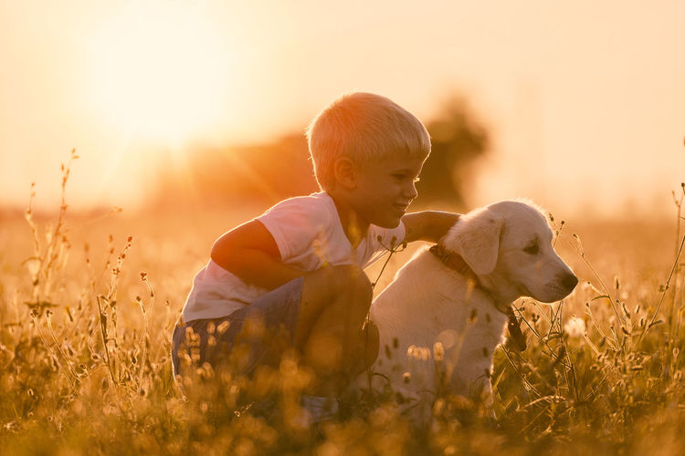 Boy with dog on field during sunset
