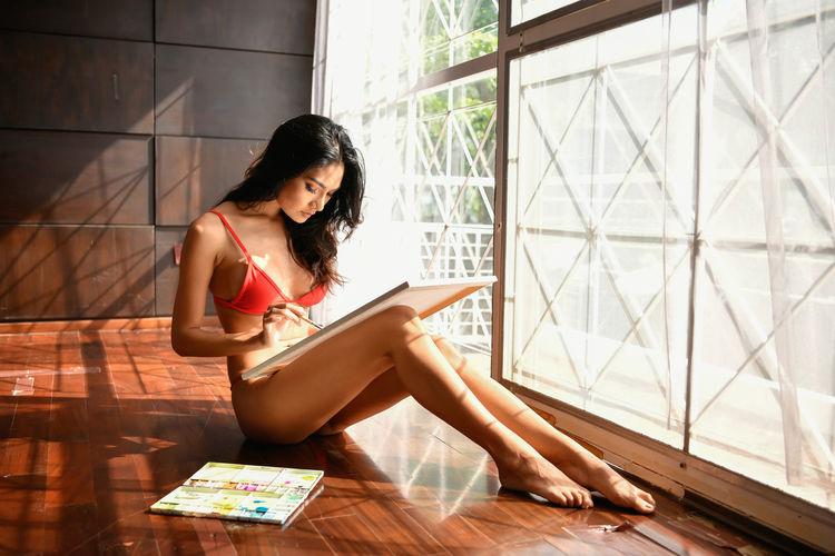 Seductive woman making painting on floorboard