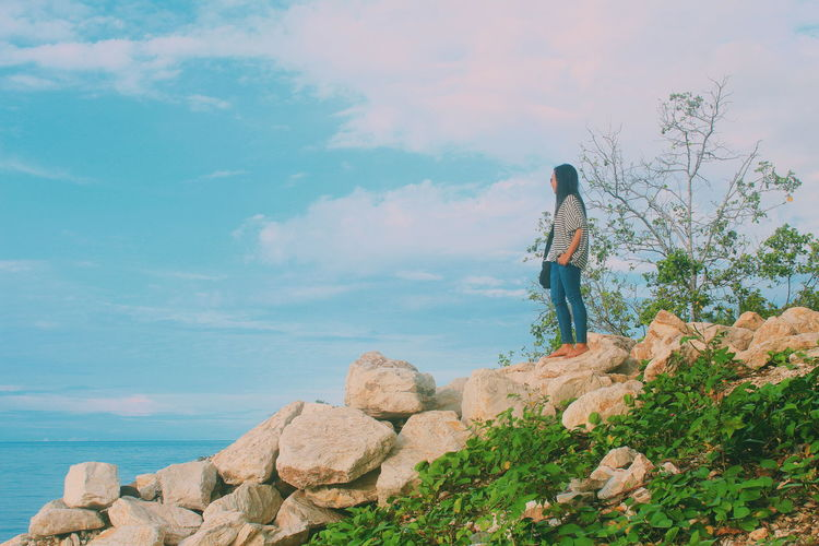 Woman standing by sea on rock against sky
