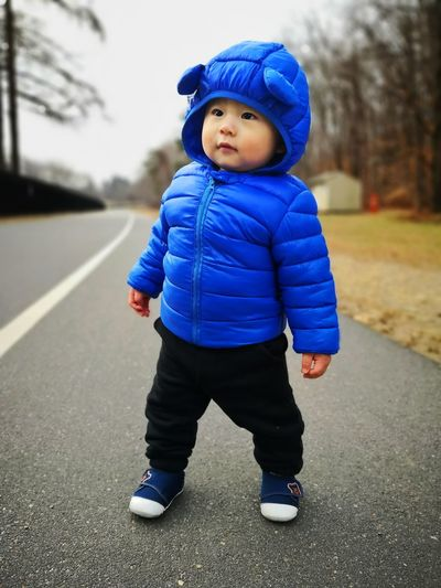 Full length of cute baby boy wearing winter jacket while standing on road