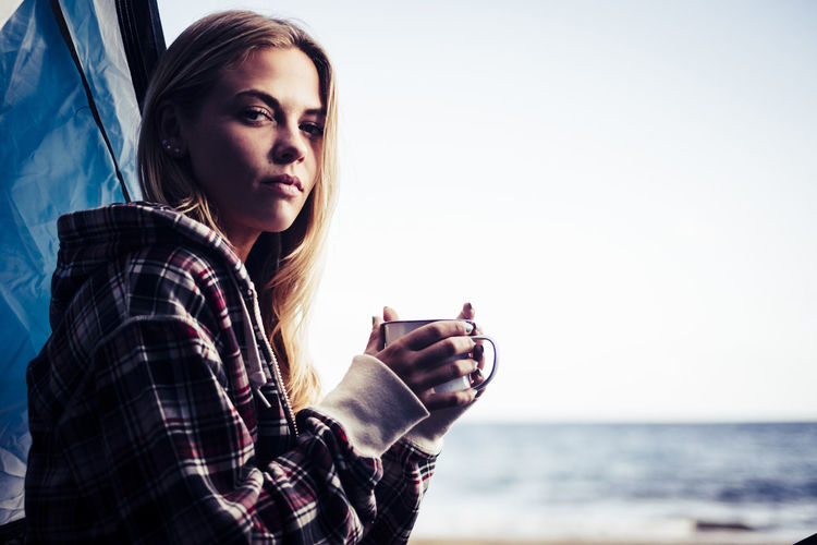 Young woman holding coffee cup by tent at beach against clear sky