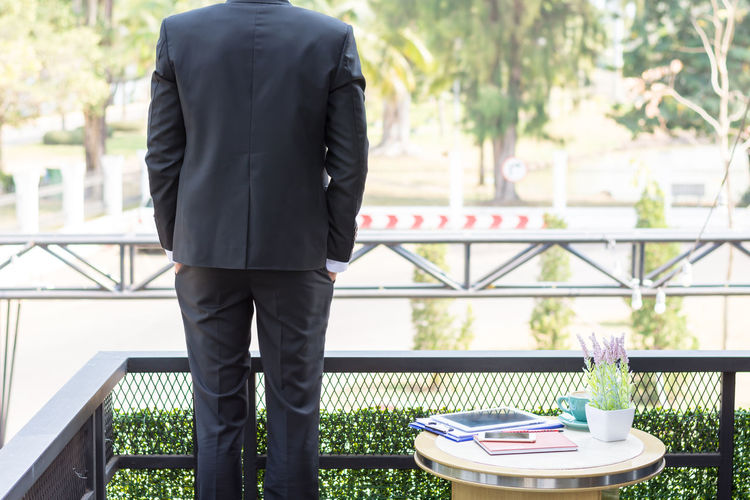 Business man standing on the balcony. Adult Architecture Business Business Person Businessman Care Day Focus On Foreground Males  Men One Person Outdoors Plant Real People Rear View Standing Suit Table Well-dressed