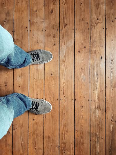 Low section of man wearing shoes standing on floorboard