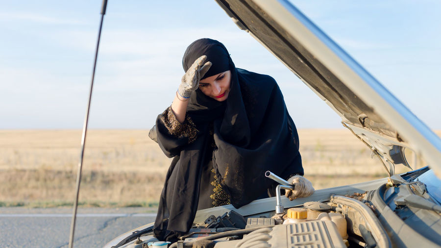 Tired woman standing by breakdown car against sky