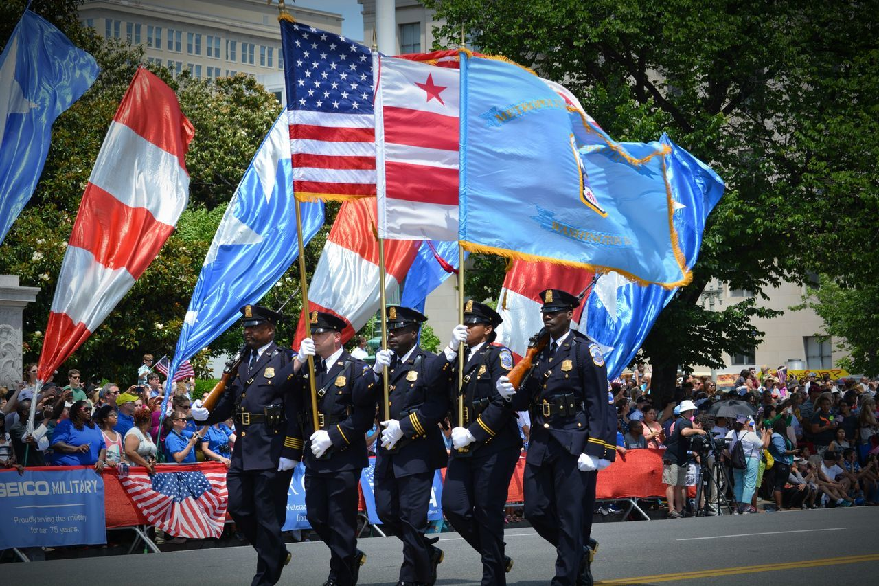 flag, patriotism, large group of people, togetherness, men, crowd, day, unity, real people, outdoors, pride, protestor, military uniform, blue, red, military parade, uniform, building exterior, tree, architecture, adult, people