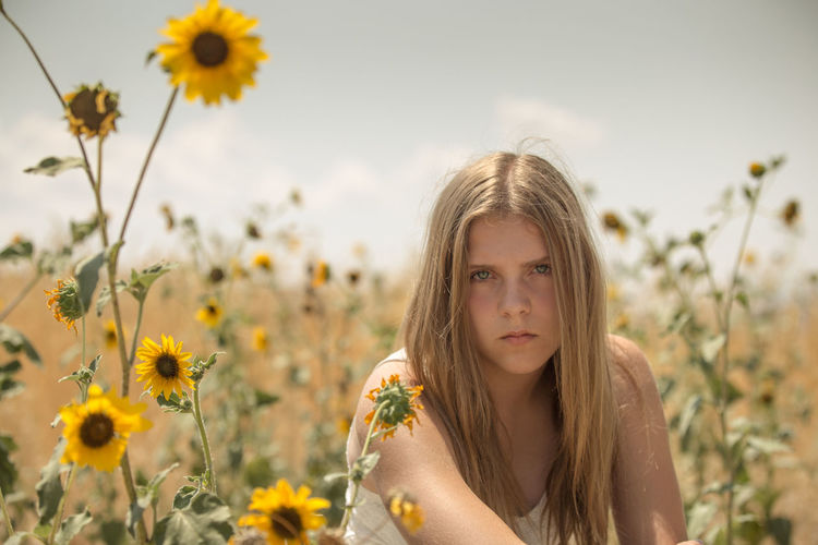 Portrait Of Woman At Flower Field On Sunny Day
