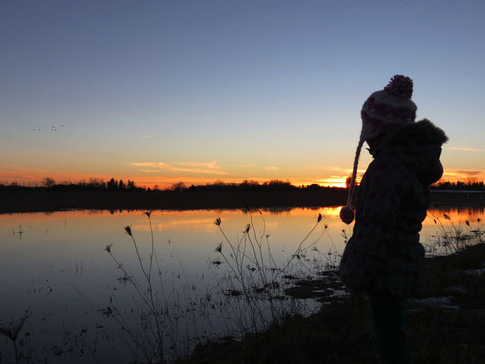 Rear View Tranquility Serenity Enjoying Life Childhood Sunset Twilight Winter Sunset Be. Ready. Calm Beauty In Nature Clear Sky Nature One Person Outdoors Real People Silhouette Standing Sunset Tranquil Scene Tranquility Water EyeEmNewHere EyeEm Ready   Lake Shades Of Winter