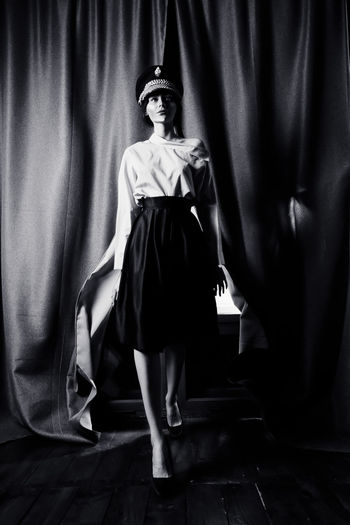 Woman Looking Away While Walking On Stage Against Curtain