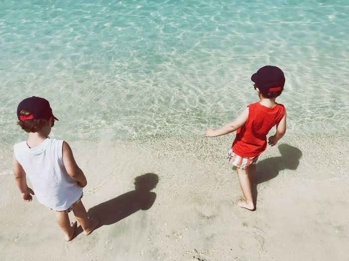 High Angle View Of Siblings Standing On Shore At Beach During Summer