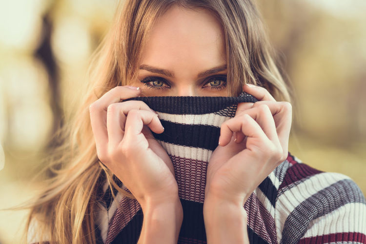 Close-up portrait of young blonde woman with blue eyes standing in the street. Beautiful girl in urban background wearing striped sweater. Female with straight hair. Blue Eyes Adult Adults Only Beautiful Woman Beauty Casual Clothing Close-up Day Focus On Foreground Front View Headshot Leisure Activity Lifestyles Looking At Camera One Person Outdoors People Portrait Real People Russian Girl Women Young Adult Young Women