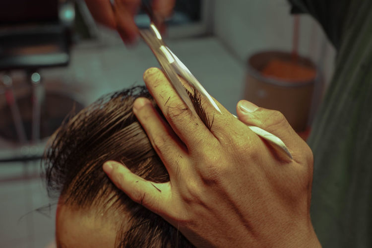 Close-up of barber cutting hair at salon