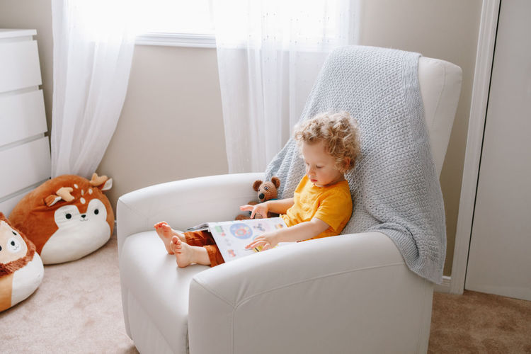 Boy toddler 2 years old sitting in armchair reading book. early age kid child development education