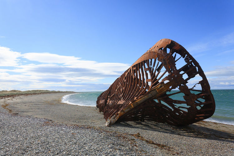 Shipwreck at beach against blue sky