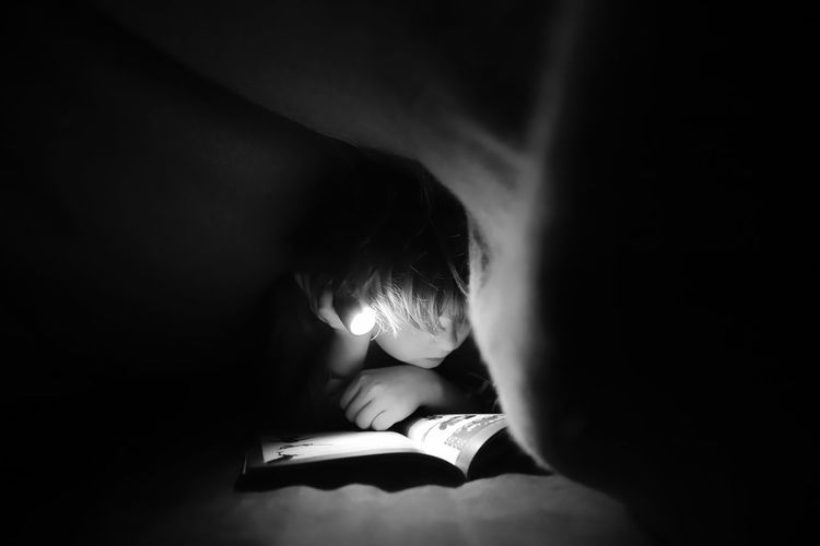 Boy With Illuminated Flashlight Reading Book In Darkroom