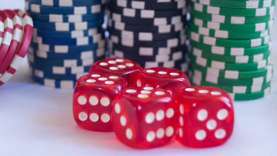 Close-Up Of Red Dice And Gambling Chips On White Table