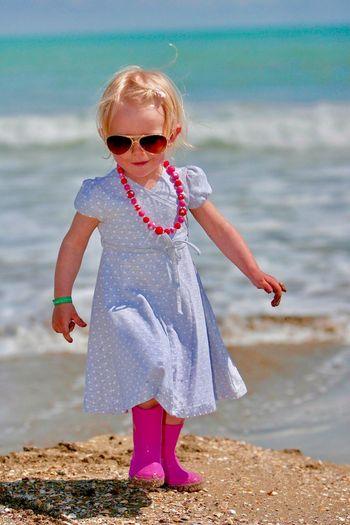 Portrait Of Cute Girl Walking On Beach