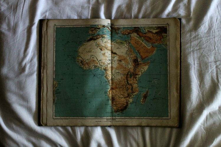 Close-up of world map book on bed sheet
