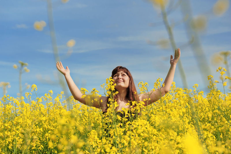 Yellow One Person Beauty In Nature Human Arm Happiness Flowering Plant Smiling Flower Leisure Activity Freshness Real People Lifestyles Plant Arms Raised Growth Sky Field Young Adult Nature Front View Limb Hairstyle Outdoors