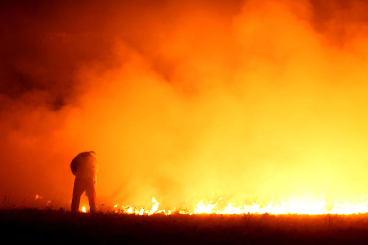 Rear View Of Firefighter Standing On Field Against Fire