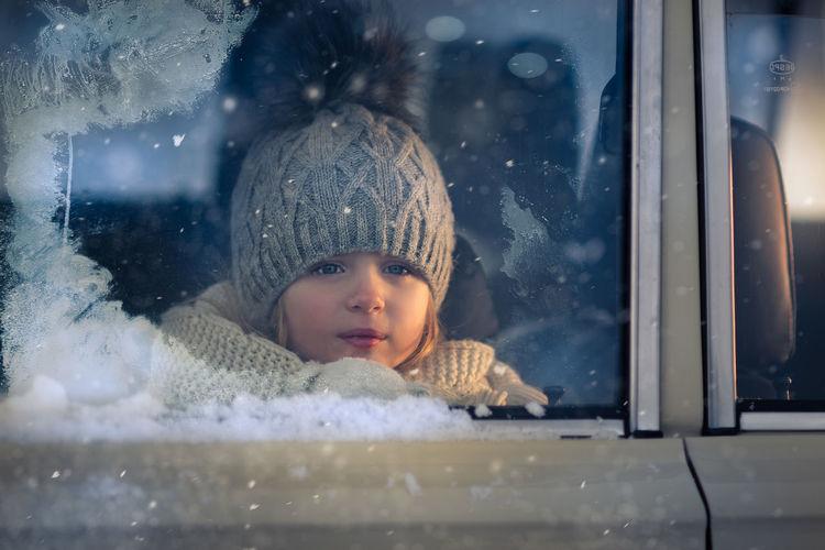 Portrait of cute girl looking through glass window