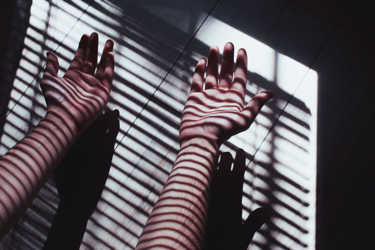 Sunlight Falling On Cropped Hands Of Woman Over Tiled Floor At Home
