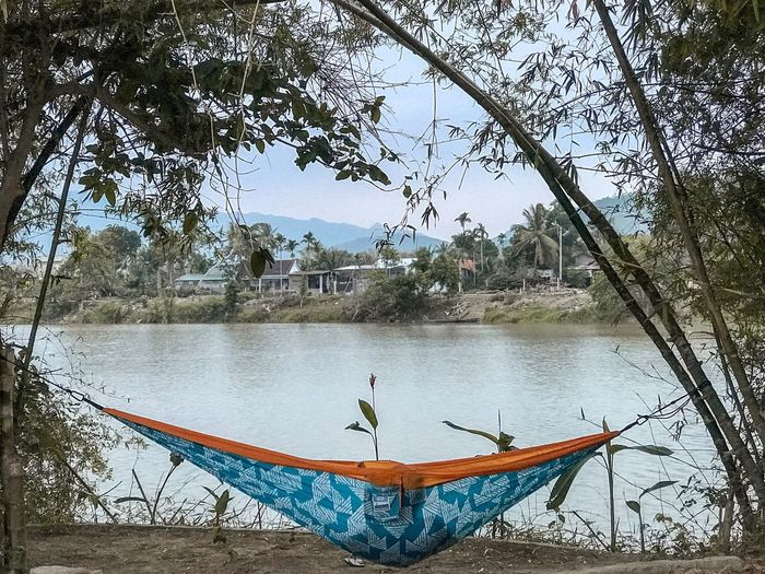 Rural Scene Village Life Village Tranquility Relaxation View Enjoying The View Lying Hammock Flow  Growth Bamboo - Plant Plant Waterfront Riverside River Water Tree Plant Real People Nature One Person Day Lifestyles Men Sky Leisure Activity Reflection Beauty In Nature Outdoors