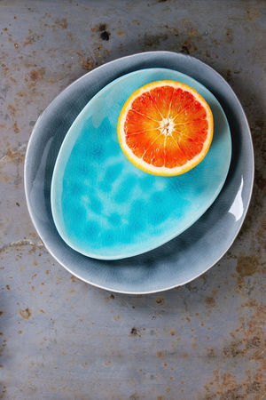 Half of Sicilian Blood orange fruit on bright turquoise and gray ceramic plates over rusty metal background. Flat lay Copy Space Sicilian Orange Bloody Orange Citrus Fruit Dark Background Directly Above Food Food And Drink Freshness Fruit Half Healthy Eating Orange Orange Color Plate Red Orange SLICE Top View Of Food Turquoise