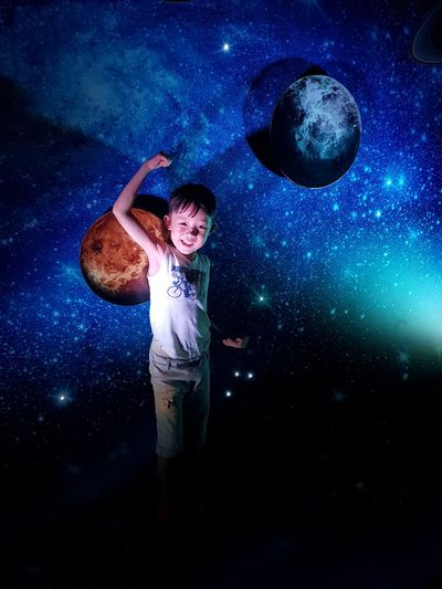 Portrait of smiling boy flexing muscles while standing against space pattern wall