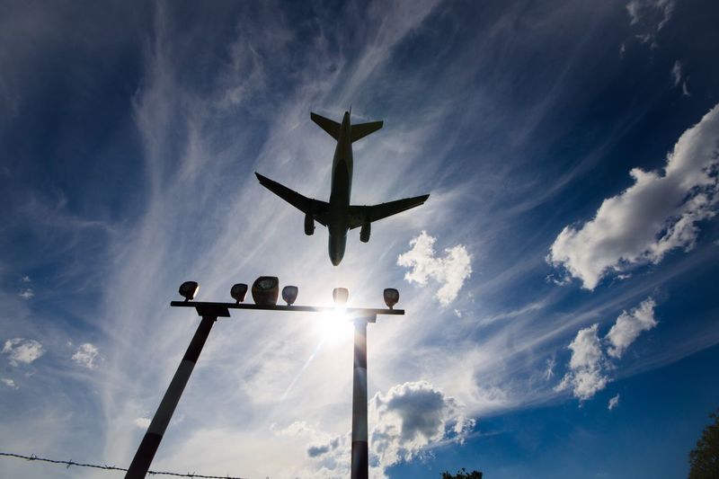 Low angle view of airplane flying over landing lights against sky at airport