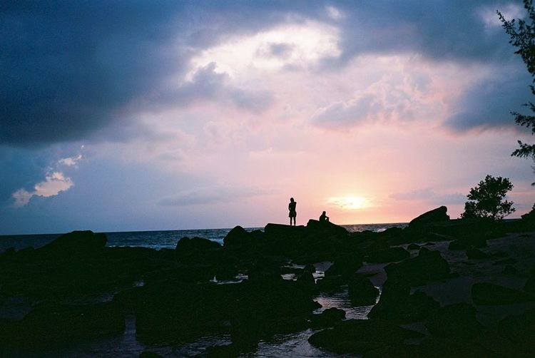 Silhouette man standing on rock by sea against sky during sunset