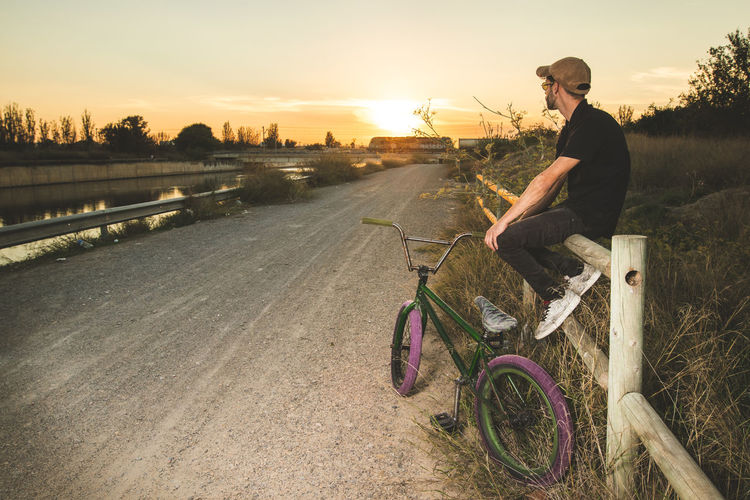 Side View Of Man Sitting With Bicycle On Road During Sunset