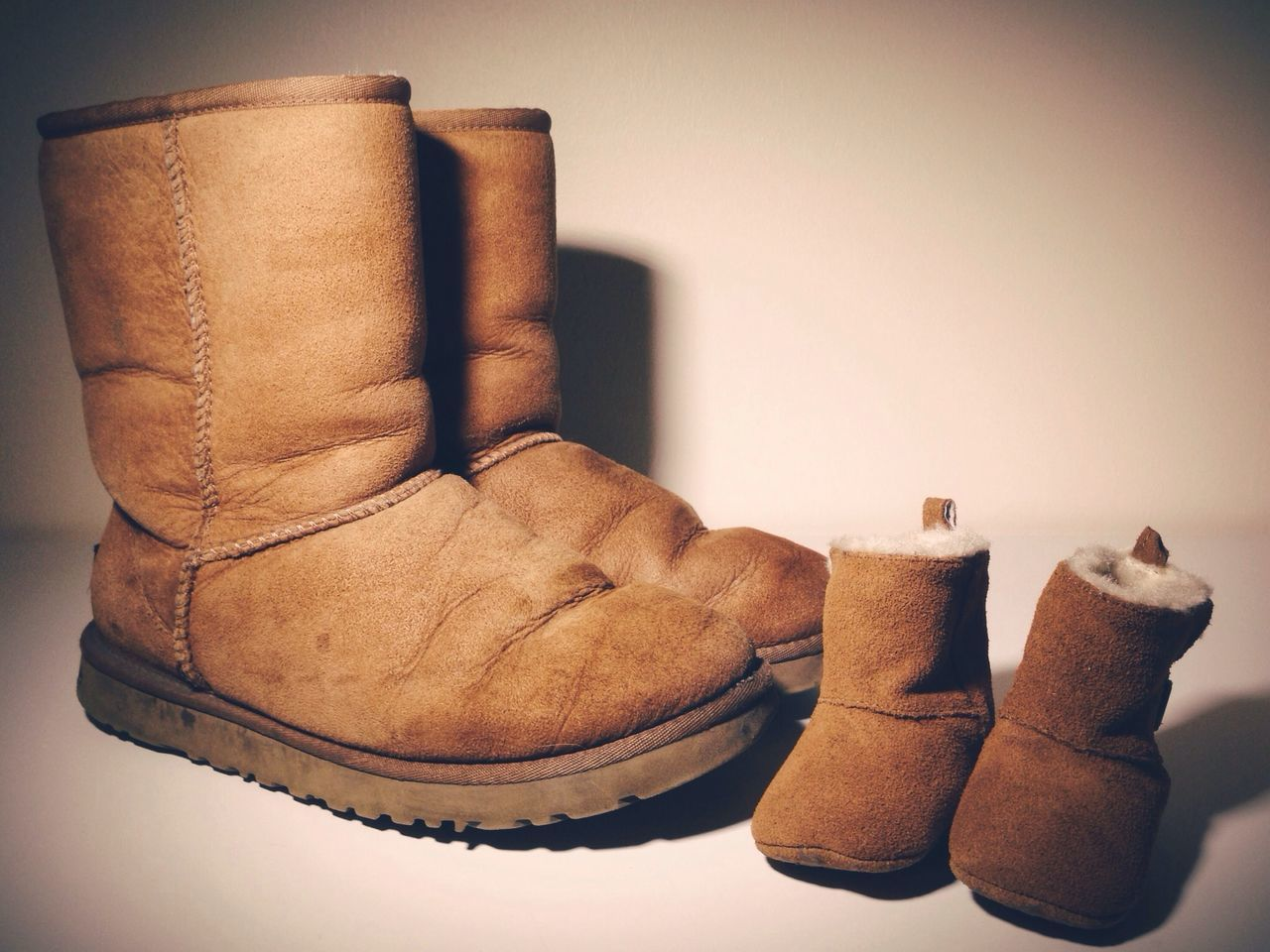 Small and big boots over white background