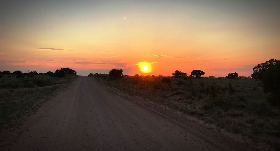"""""""Blaze Of Glory"""" A lonely county road in Central New Mexico leads a soul to fade into the sunset. New Mexico Skies New Mexico New Mexico Photography Country Road Evening Sky Sunset Silhouettes Sunset_collection Sunsets Dusk Sundown Sunset Sky Landscape Scenics - Nature Road Dirt Road Orange Color"""