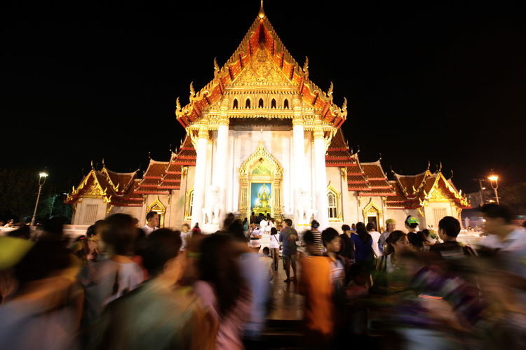 Blurred motion of people at illuminated wat benchamabophit against sky