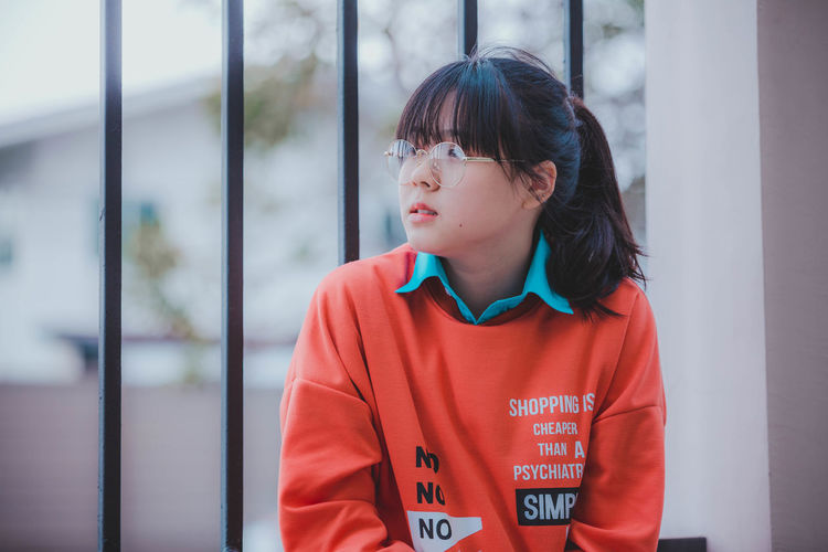 One Person Looking Looking Away Standing Real People Casual Clothing Black Hair Front View Waist Up Focus On Foreground Hair Lifestyles Women Females Hairstyle Innocence Bangs Contemplation Fashion Fashion Photography Close-up women around the world Young Adult Orange Color