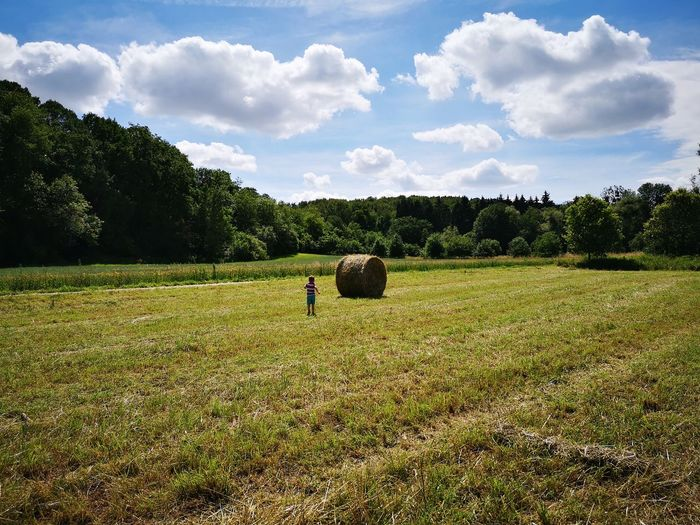 Boy Walking Against Hay Bale On Field In Sunny Day
