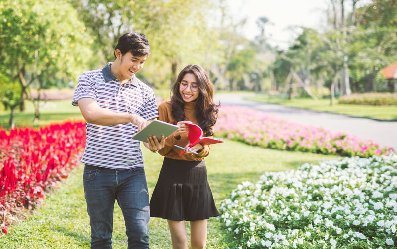 Cheerful friends looking at book in public park