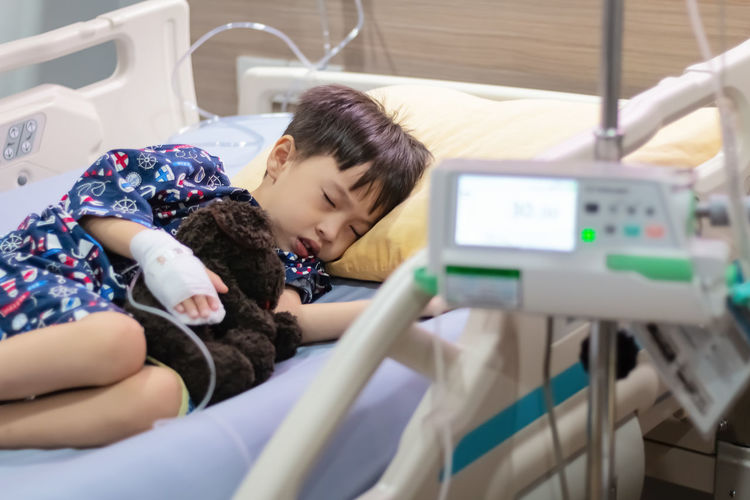 Cute patient with toy lying bed in hospital