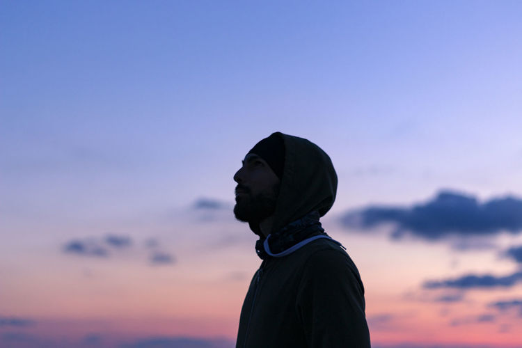 Thoughtful man standing against sky during sunset