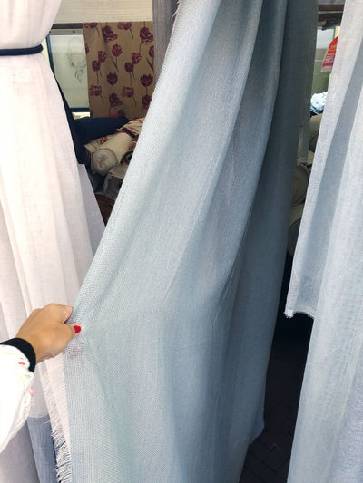 Midsection of woman standing by curtain