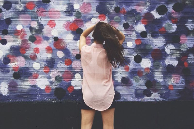 Rear View Of Woman With Arms Raised Holding Hair Against Graffiti Wall